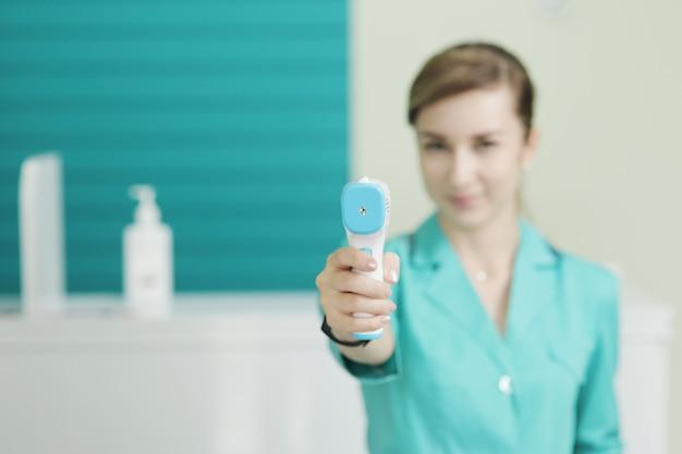 Vrouwelijke arts of verpleegkundige in het ziekenhuis houdt pyrometer in de hand