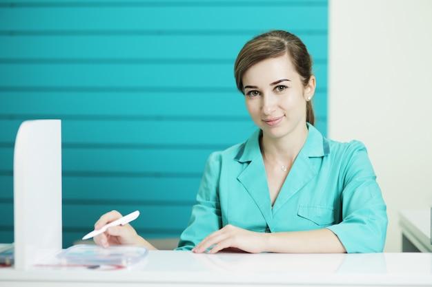 Vrouwelijke arts of verpleegkundige in medisch uniform kijken naar de camera.
