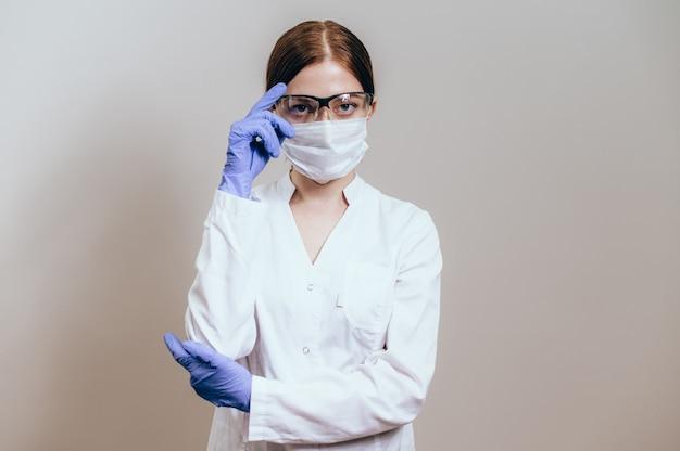 Vrouwelijke arts of verpleegster die een beschermend gezichtsmasker en een veiligheidsbril draagt. vrouw arts in een witte jas draagt een beschermend masker voor werk