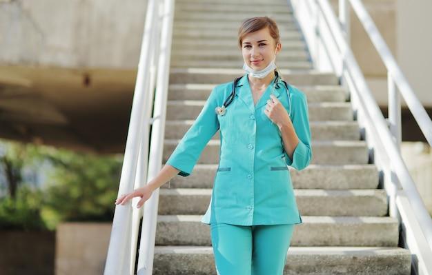 Vrouwelijke arts of verpleegster die een beschermend masker en medische kleding draagt, een stethoscoop om haar nek