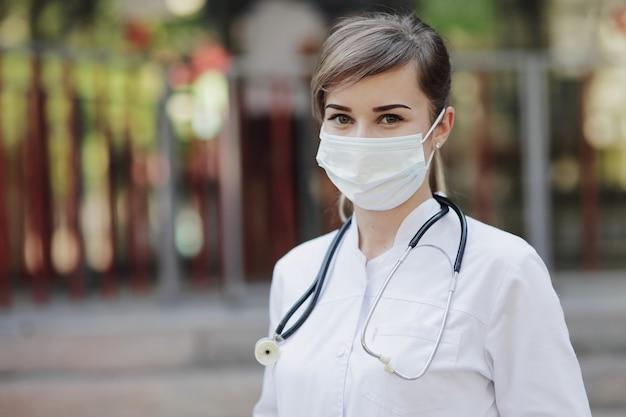 Vrouwelijke arts of verpleegster die een beschermend masker met een stethoscoop om haar hals draagt