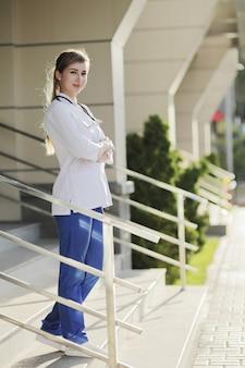 Vrouwelijke arts of verpleegster in medisch uniform op de trappen van het ziekenhuis