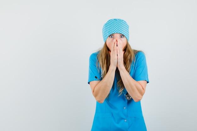 Vrouwelijke arts omklemde handen in de buurt van open mond in blauw uniform en kijkt geschokt.