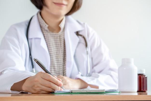 Vrouwelijke arts ondertekende een document op houten tafel.