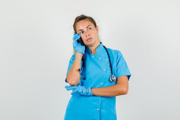 Vrouwelijke arts opzij kijken tijdens het praten over smartphone in blauw uniform