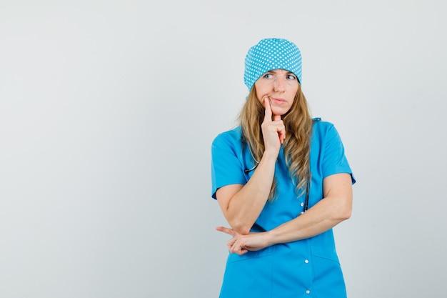 Vrouwelijke arts permanent in denken pose in blauw uniform en aarzelend op zoek.