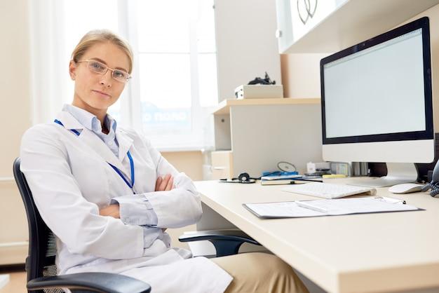 Vrouwelijke arts poseren aan balie