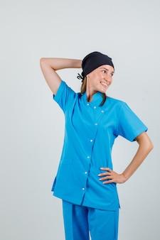Vrouwelijke arts poseren met handen op hoofd en taille in uniform en op zoek vrolijk. vooraanzicht.