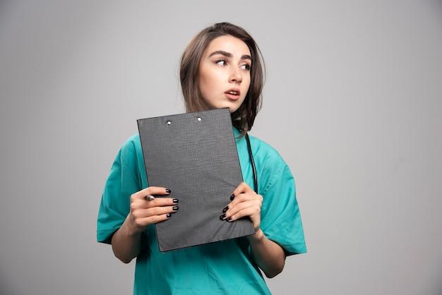 Vrouwelijke arts poseren met klembord op grijze achtergrond. hoge kwaliteit foto
