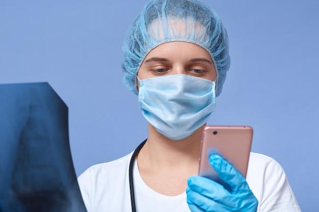 Vrouwelijke arts praten aan de telefoon in het ziekenhuis of kantoor kliniek, onderzoek van de ruggengraat, bel haar collega om zijn bevindingen te bespreken