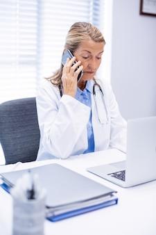 Vrouwelijke arts praten op mobiele telefoon