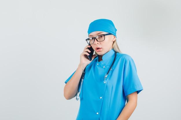 Vrouwelijke arts praten over smartphone in blauw uniform, glazen en hulpeloos op zoek.