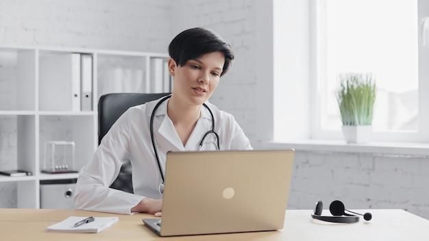 Vrouwelijke arts raadplegen patiënt op afstand online met behulp van webcamera op laptop