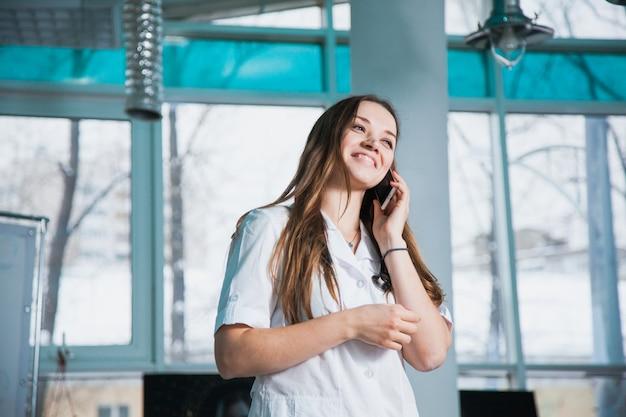 Vrouwelijke arts raadplegende patiënt via de mobiele telefoon. bespreek de diagnose telefonisch in de kliniek. gezondheid geneeskunde diagnostiek concept