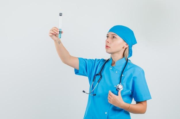 Vrouwelijke arts reageerbuis in blauw uniform houden