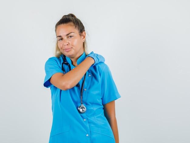 Vrouwelijke arts schouder wrijven voor ontspanning in blauw uniform