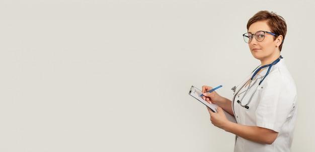 Vrouwelijke arts schrijft met een pen een document op een tablet, schrijft een medische geschiedenis. het concept van de gezondheidszorg, geneeskunde