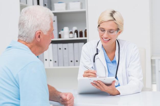 Vrouwelijke arts schrijven recept voor senior man in de kliniek