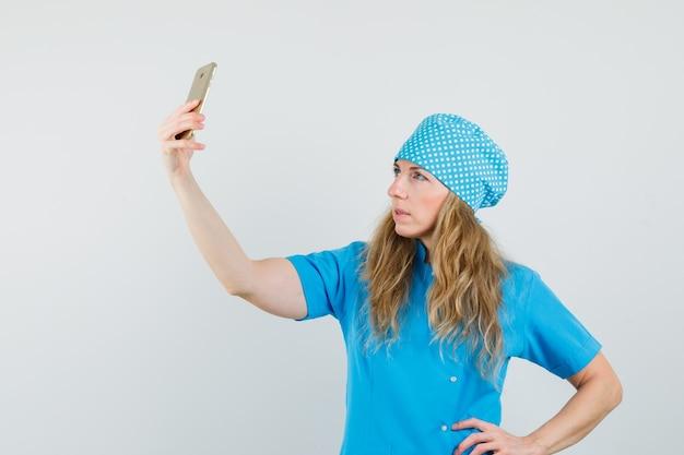 Vrouwelijke arts selfie te nemen op mobiele telefoon in blauw uniform