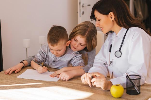 Vrouwelijke arts spelen met kleine patiënten in office