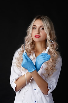 Vrouwelijke arts staat met een gadget voor gezichtshuid