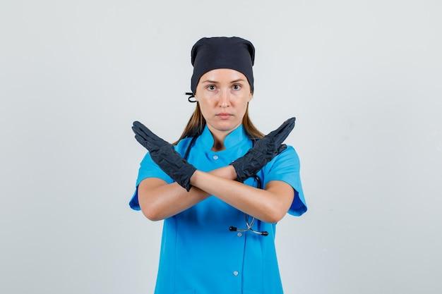 Vrouwelijke arts stop gebaar in uniform, handschoenen en uitgeput op zoek. vooraanzicht.