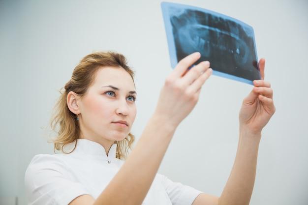 Vrouwelijke arts-tandarts die x-ray van menselijke kaak onderzoekt. professionele stomatologist tandheelkundige x-ray beeld controleren op kantoor van de kliniek.