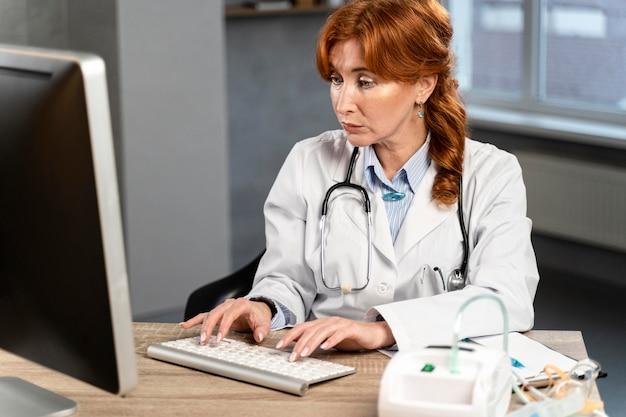 Vrouwelijke arts te typen op de computer bij het bureau