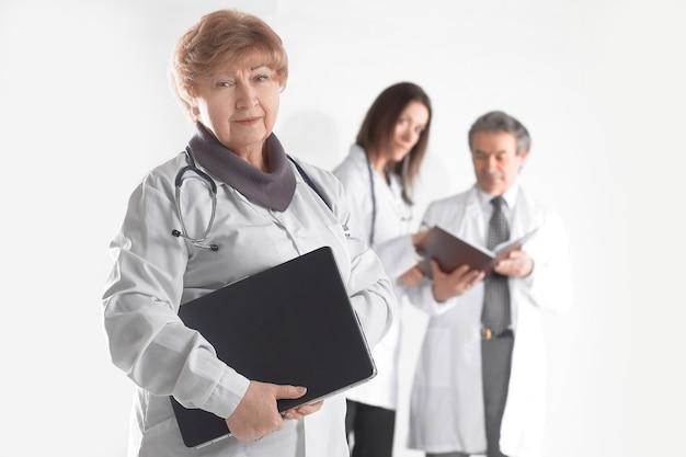 Vrouwelijke arts-therapeut met laptop op onscherpe achtergrond van collega's