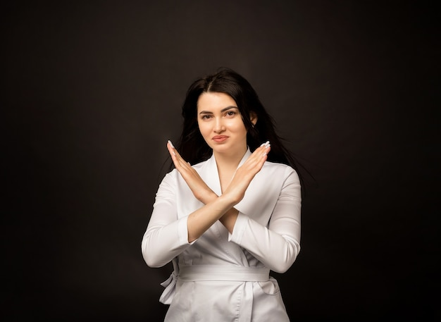 Vrouwelijke arts toont handen verbieden teken op zwart