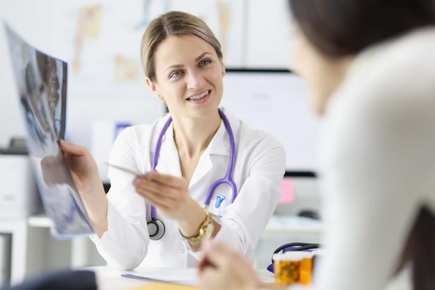 Vrouwelijke arts toont patiënt een xray-close-up