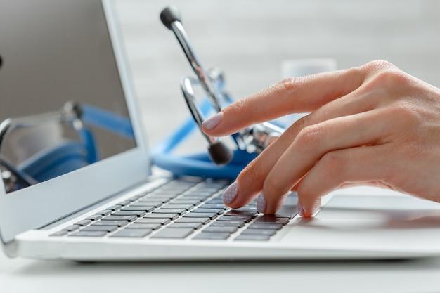 Vrouwelijke arts typt laptopcomputer