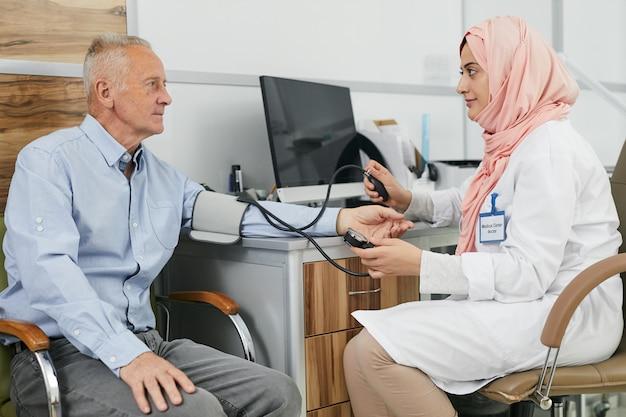 Vrouwelijke arts uit het midden-oosten die met hogere patiënt spreekt