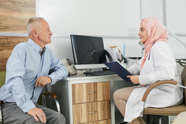 Vrouwelijke arts uit het midden-oosten die senior patiënt raadpleegt
