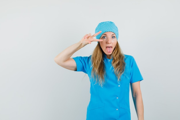 Vrouwelijke arts v-teken in de buurt van oog tonen en tong in blauw uniform uitsteekt