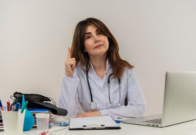 Vrouwelijke arts van middelbare leeftijd draagt ?? het dragen van medische mantel met stethoscoop zittend aan een bureau werken op laptop met medische hulpmiddelen wijst naar boven op geïsoleerde witte muur met kopie ruimte