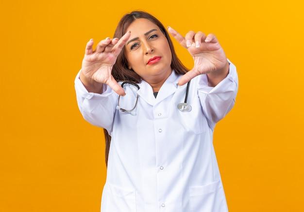 Vrouwelijke arts van middelbare leeftijd in witte jas met stethoscoop die een frame maakt met vingers die door dit frame kijken en zelfverzekerd glimlachen