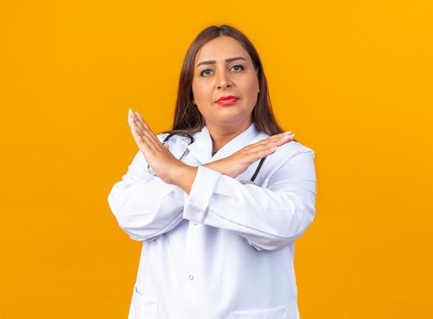 Vrouwelijke arts van middelbare leeftijd in witte jas met stethoscoop die met een serieus gezicht kijkt en een stopgebaar maakt dat de handen kruist