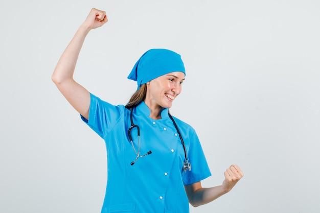 Vrouwelijke arts vieren overwinning met opgeheven vuisten in blauw uniform en op zoek gelukkig