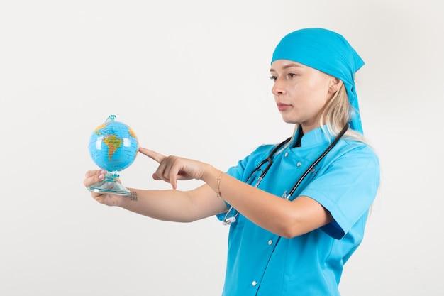 Vrouwelijke arts vinger op wereldbol om een bestemming in blauw uniform te kiezen.