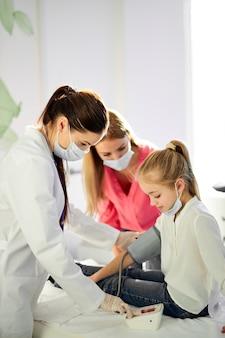 Vrouwelijke arts vrouw bloeddruk meten van meisje met tonometer, gezondheid, coronavirus, covid-19, griep concept controleren. in moderne ziekenhuiskamer