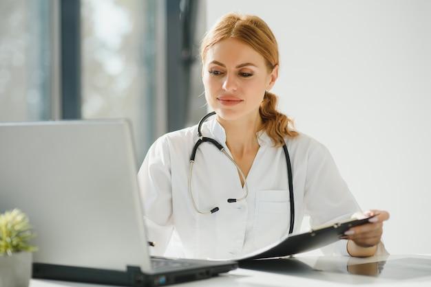 Vrouwelijke arts werkzaam bij bureau en glimlachend in de camera, kantoor interieur op achtergrond