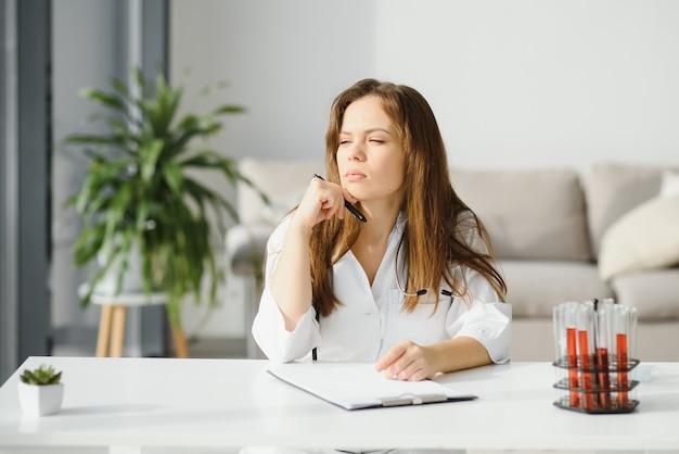 Vrouwelijke arts werkzaam bij bureau, kantoor interieur op achtergrond