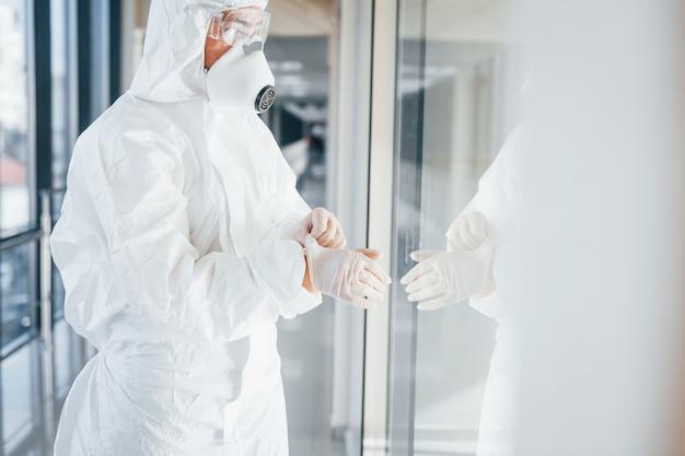 Vrouwelijke arts wetenschapper in laboratoriumjas, defensieve brillen en masker permanent binnenshuis en het dragen van handschoenen
