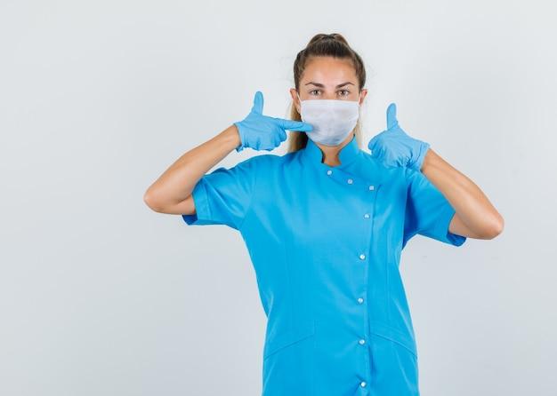 Vrouwelijke arts wijzend op masker met duim omhoog in blauw uniform, handschoenen en voorzichtig kijken