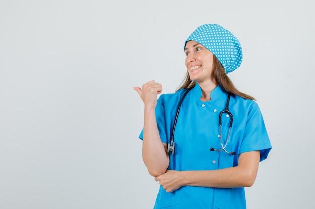 Vrouwelijke arts wijzende duim terug in blauw uniform en ziet er vrolijk uit