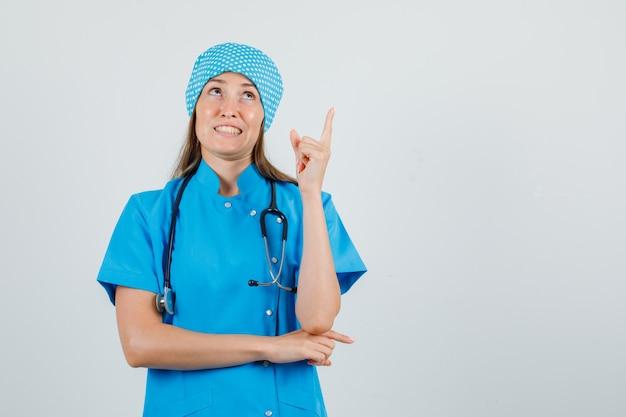 Vrouwelijke arts wijzende vinger in blauw uniform en bang op zoek. vooraanzicht.