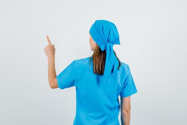Vrouwelijke arts wijzende vinger naar iets in blauw uniform.