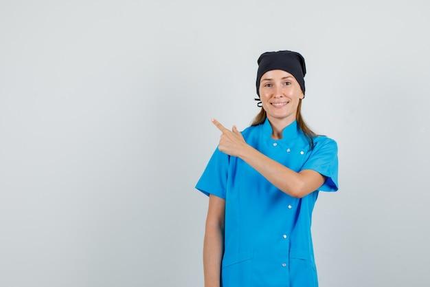 Vrouwelijke arts wijzende vinger naar kant in blauw uniform, zwarte hoed en op zoek vrolijk