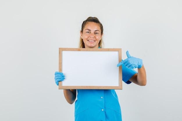 Vrouwelijke arts wijzende vinger op wit bord in blauw uniform